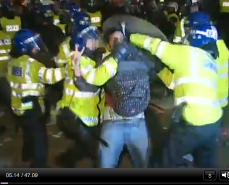 riot police restraining student at Millbank invasion
